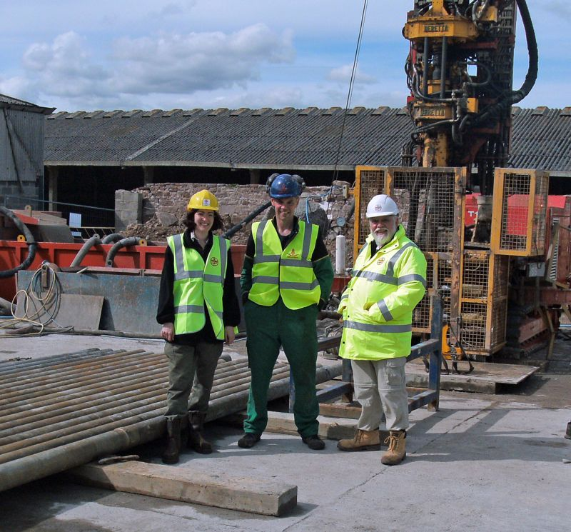 Carys Bennett (Uni. of Leicester), Alistair Birkett (landowner) and Dave Millward (BGS) standing in front of the rig.